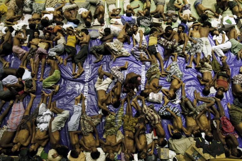 Migrants believed to be Rohingya rest inside a shelter after being rescued from boats at Lhoksukon in Indonesia's Aceh Province on May 11, 2015.  REUTERS/Roni Bintang
